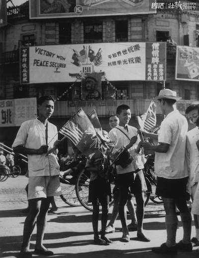 circa 1945:  Residents of Shanghai buy flags of the United Nations to celebrate VJ Day, when the formal Japanese surrender was signed aboard the US battleship Missouri, in Tokyo Bay.  (Photo by Fox Photos/Getty Images)