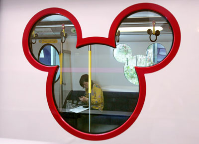 A reporter sits in the new Disneyland Resort Line train in Hong Kong April 25, 2005. The entertainment park launched the Disneyland train which will bring visitors to China's first Disney theme park when it opens on September 12. REUTERS/Kin Cheung